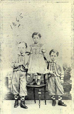 Η αρχή ενός μύθου. Ο Καβάφης δύο ετών ανάμεσα στ αδέρφια του. Ημερομηνία γραμμένη από τον ίδιο. Η μητέρα επέμενε να ντύνει τον Κωνσταντίνο με γυναικεία ρούχα.. (kavafis.gr)